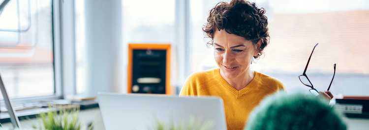Smiling woman on laptop reviewing her options