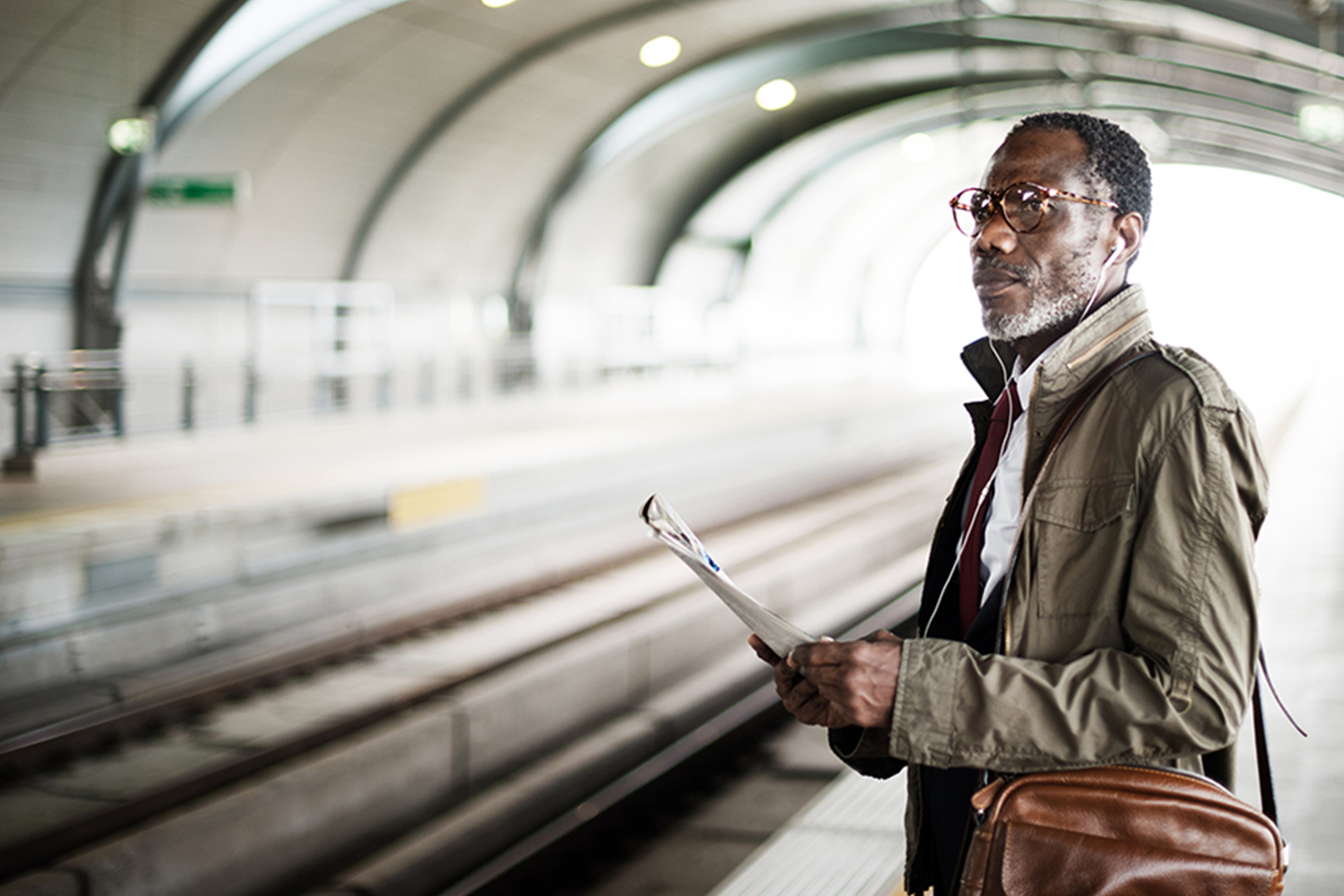 middle_aged_black_man_with_magazine_at_train_station_Banner_Block_2120px