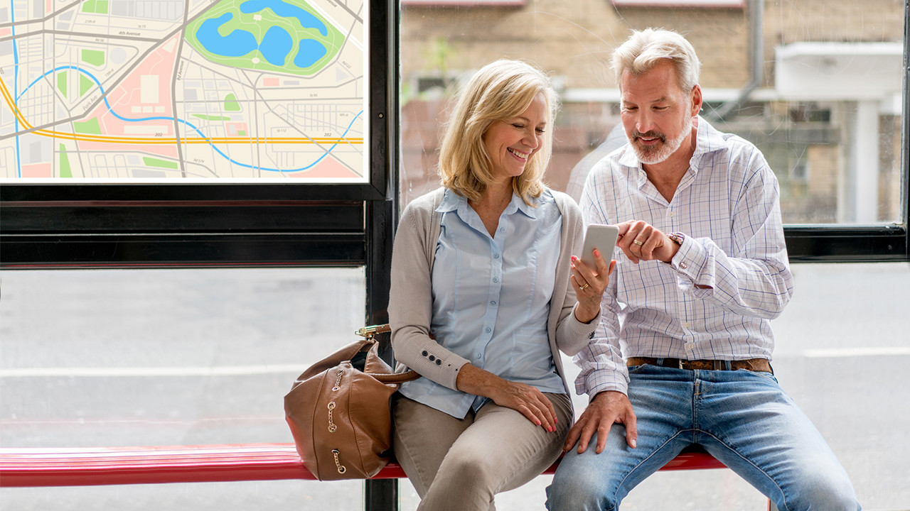 middle_aged_couple_on_phone_at_bus_stop_Banner_Block_1280px