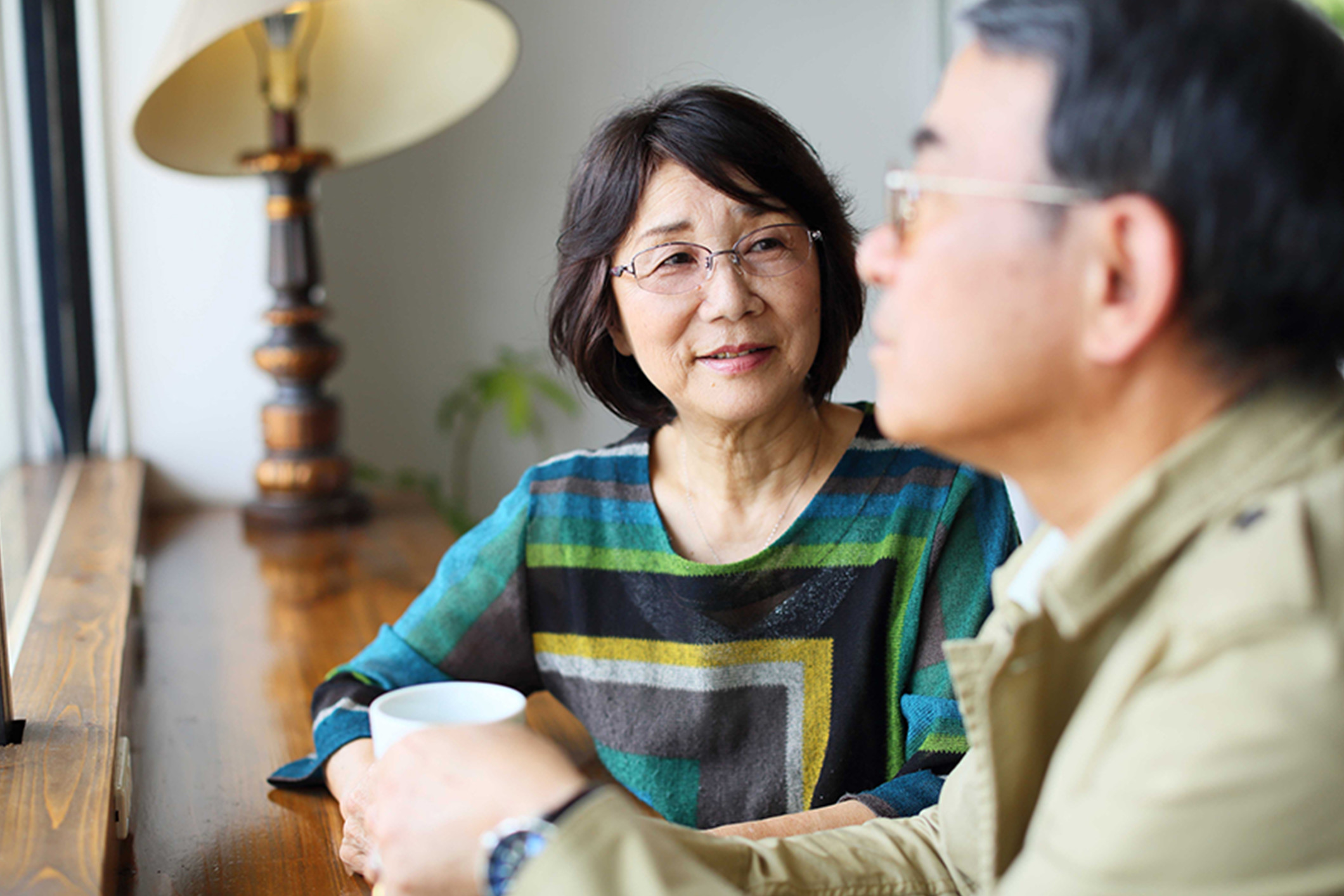 older_asian_couple_discussion_over_tea_Banner_Block_2120px