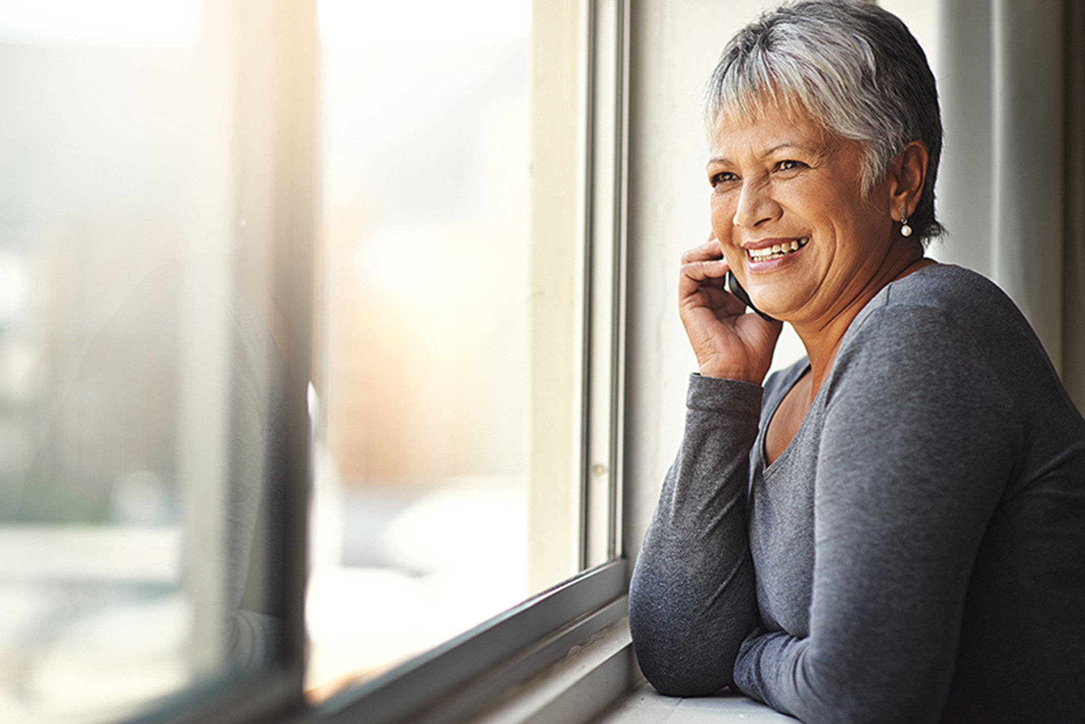 older_woman_on_phone_looking_out_window_Banner_Block_2120px
