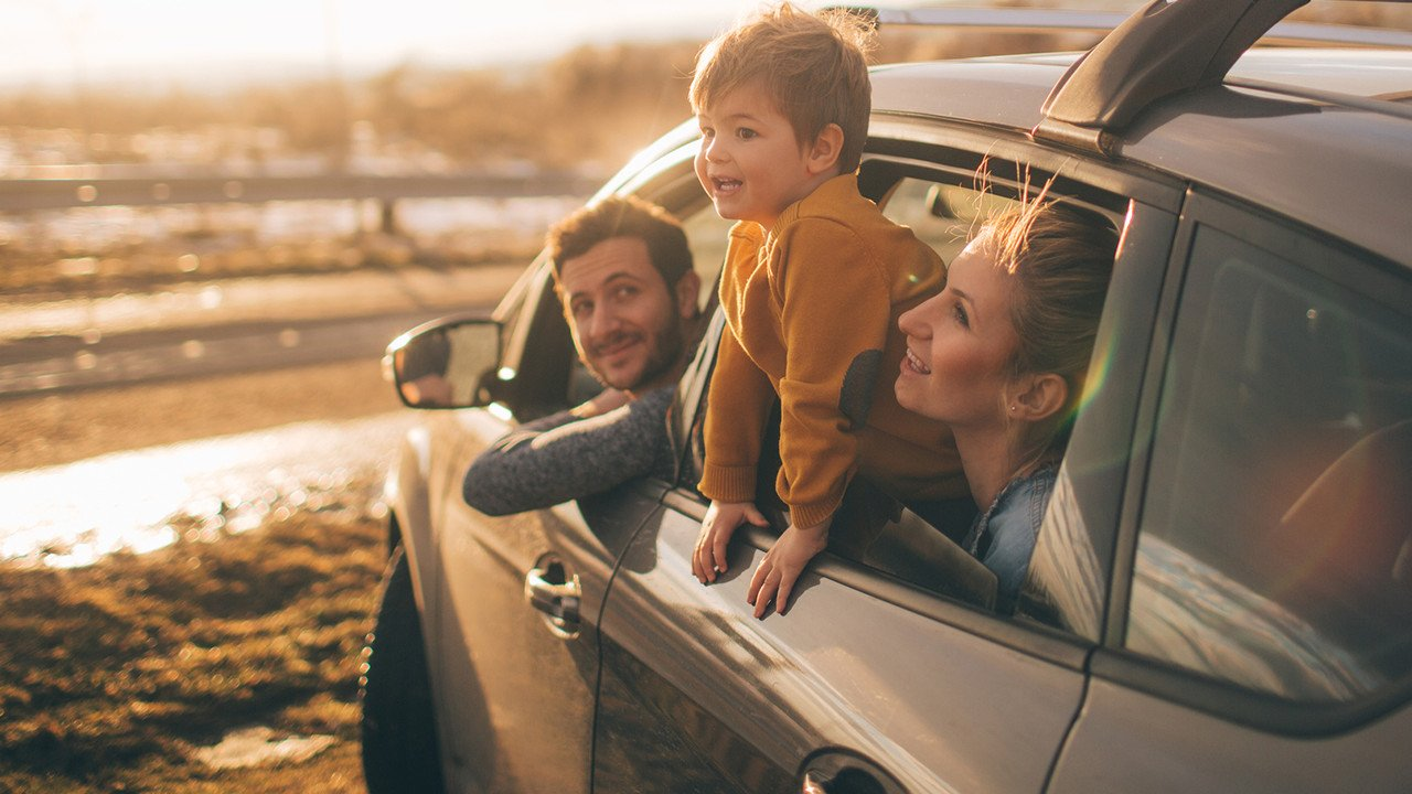 Young Family Leaning Out of Car Window