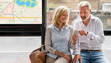 middle_aged_couple_on_phone_at_bus_stop_Feature_box_355px