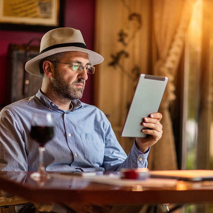businessman_relaxing_in winebar_on_tablet_square&circle_720px