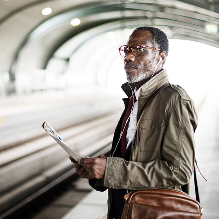 middle_aged_black_man_with_magazine_at_train_station_square&cirle_720px