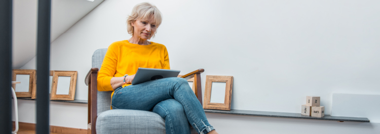 Woman in yellow top in armchair looking at laptop