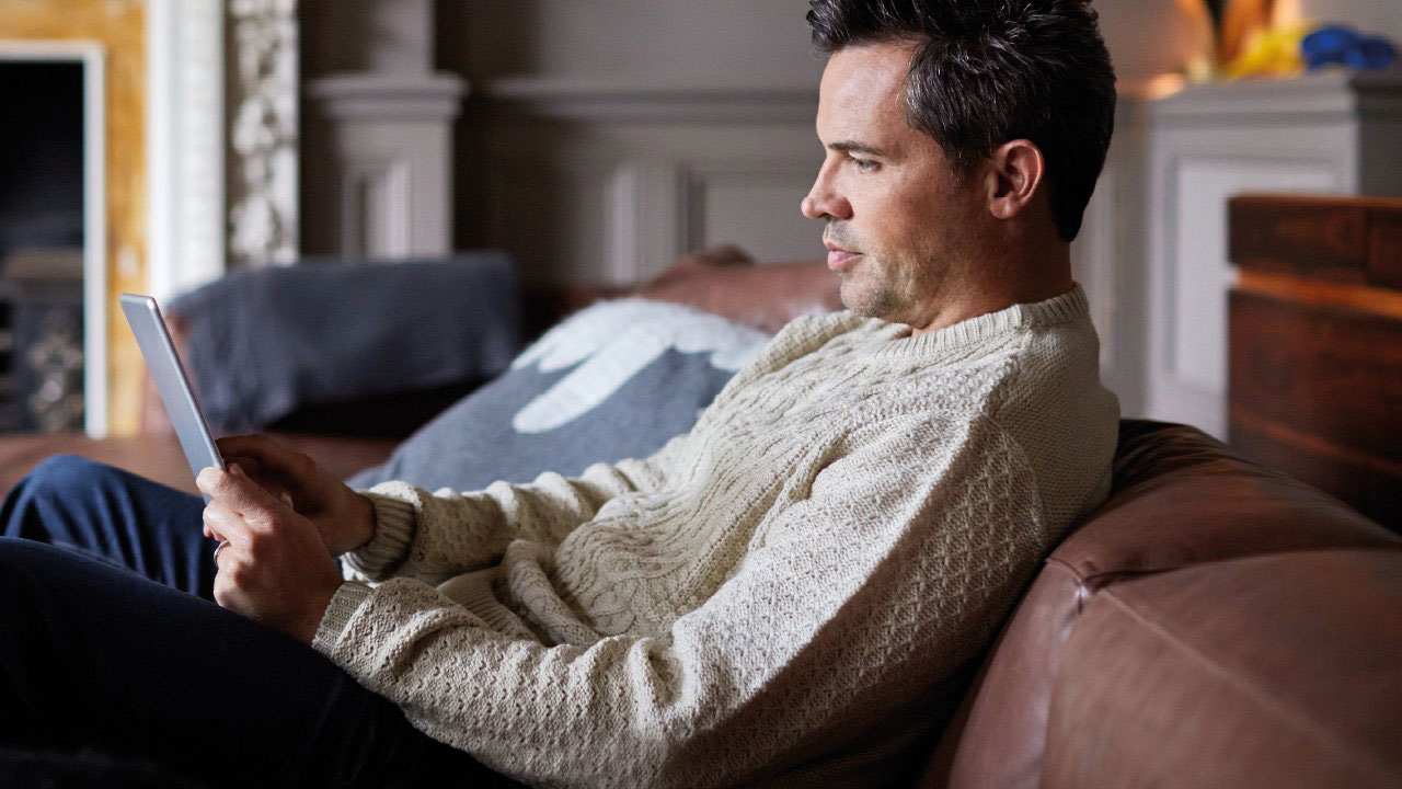 Man in his home looking at tablet device