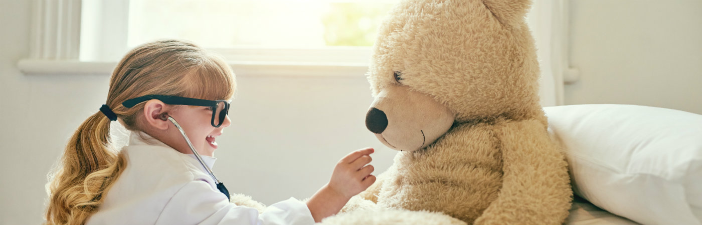 Little girl playing doctors with her teddy bear - Life insurance vs health insurance
