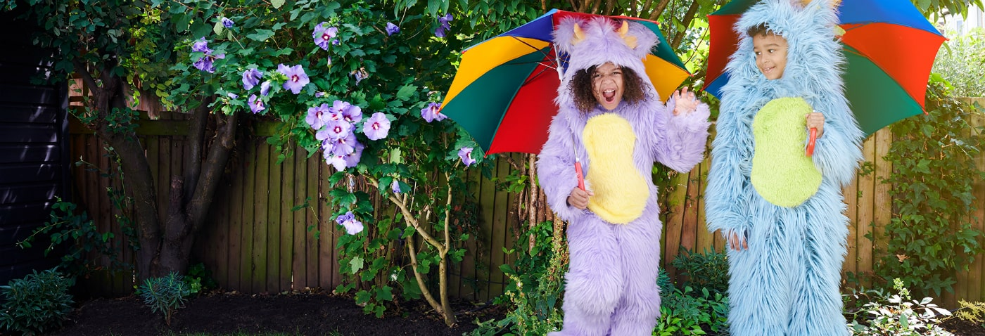 Two kids dressed in a blue and purple furry monster suit holding umbrellas while roaring