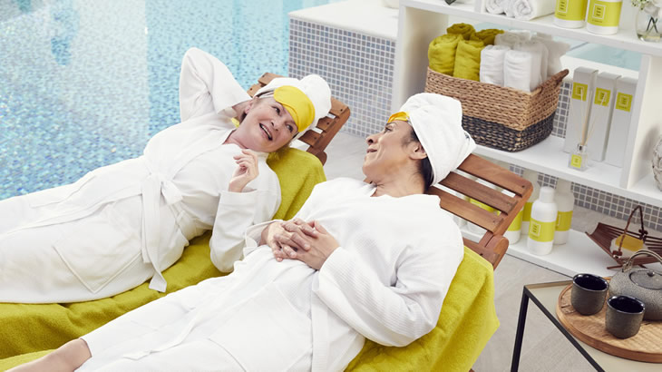 Two women relax by the pool in a spa.