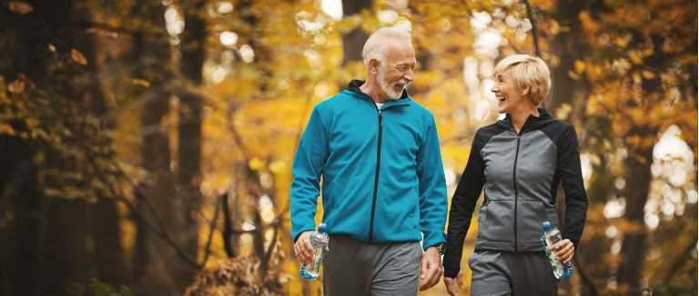 Mature active couple walking in park